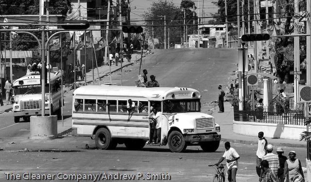 Two buses filled with armed men drive through the streets of Port-au-Prince on February 29, 2004, the day that Jean Bertrand Aristide was deposed as Haiti's president.