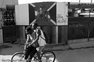 Residents of St. Marc cycle past painting of late Jamaican reggae superstar, Bob Marley on the streets on St. Marc on February 22, 2004.