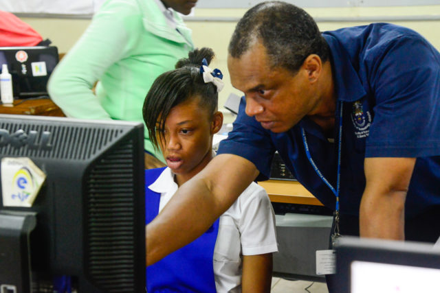 Workshop facilitator Andrew Smith of UTech Jamaica assists a student of Buff Bay High School during a heritage education workshop organised in Buff Bay, Portland on November 1 2016.